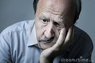 Head portrait of senior mature old man on his 70s looking sad and worried suffering Alzheimer disease