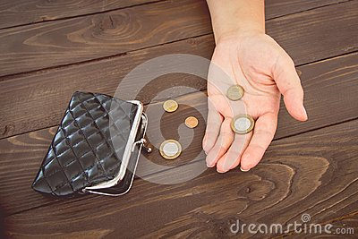 Old empty wallet and coins in the hands .Vintage empty purse and coins in hands of women . Poverty concept. Bankruptcy