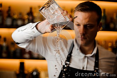 Young barman pouring water from a glass with ice cubes