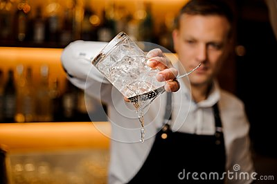 Bartender pouring water from a glass with ice cubes