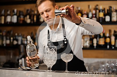 Barman pouring a portion of vodka into a glass