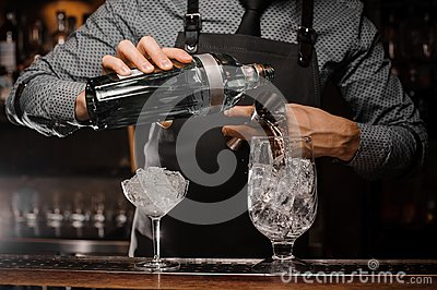 Barman pouring alcoholic drink into a glass using a jigger to prepare a cocktail