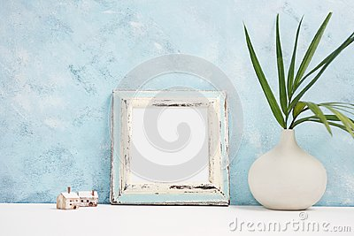 Square blue Photo frame mock up with green tropical plants in vaseand small wooden houses on shelf. Scandinavian style