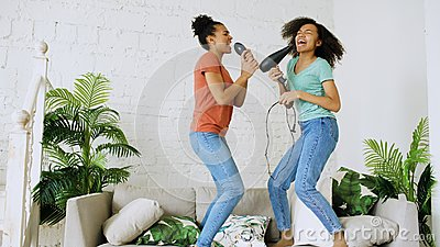 Mixed race young funny girls dance singing with hairdryer and comb jumping on sofa. Sisters having fun leisure in living