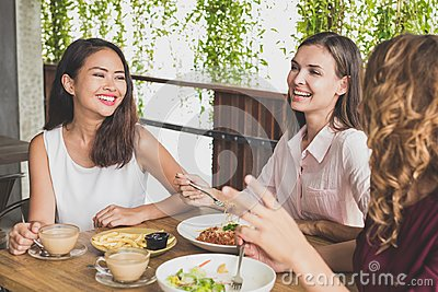 Group of three best friend having fun conversation while lunch t