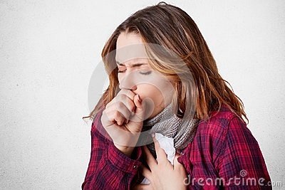 Studio shot of beautiful young female model has bad cough, uses tissue, wears scarf on neck, feels unwell and unhealthy,
