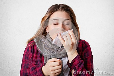 Beautiful female wears warm scrf, sneezes into tissue, suffers from cold and high tempreture, has flue, tries to cure herself, iso