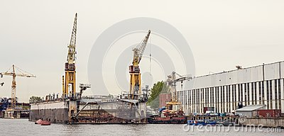 Cargo ship loading cranes in industrial zone on river, freight logistic transportation by water concept