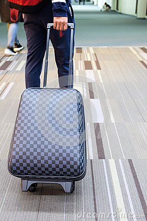 Young traveler man dragging luggage at airport