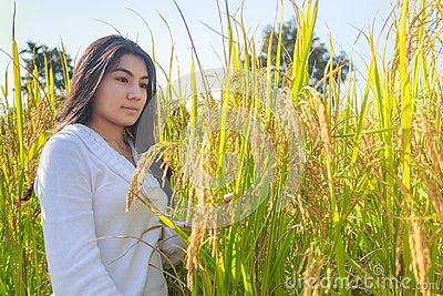 Asian woman in the green rice fields meadow