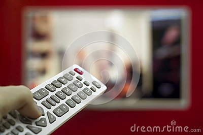 The remote in the hand switch channels on the TV hanging on the red wall