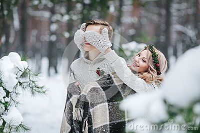 Cute girl covering boyfriend`s eyes by her knitted mittes. Winter wedding. Artwork.