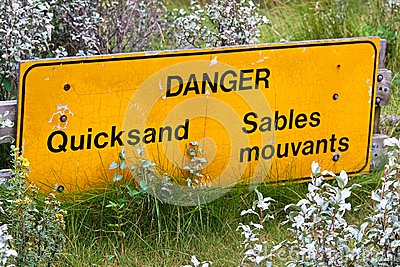 Closeup of a bilingual danger quicksand sign