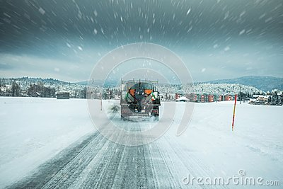 Winter service truck or gritter spreading salt on the road surface to prevent icing in stormy snow winter day.