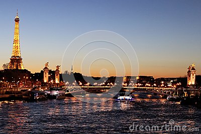 River Seine Paris by night with Alexandre III bridge and Eiffel Tower illuminated france
