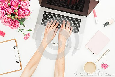 Home office desk. Woman workspace with female hands, laptop, pink roses bouquet, accessories, diary on white. Top view. Flat lay.