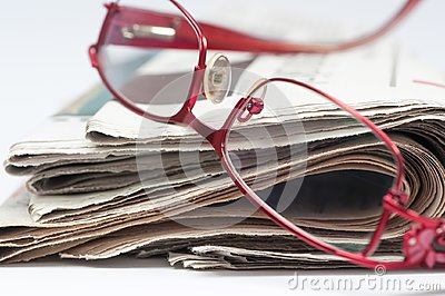 Red eyeglass on a stack of folded newspaper.