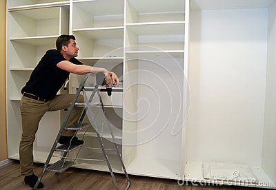 Worker looking at wardrobe. Cabinet assembly concept.