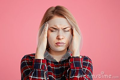 Depressed stressful female has headache, keeps hands on temples, closes eyes as feel terrible pain, being overworked and fatigue,