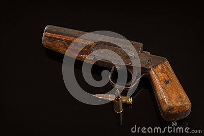 Vintage retro handgun pistol and two bullets isolated on black background