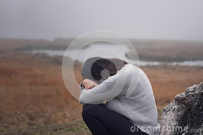 Young woman leaning against a stone with arms crossed in front of the face crying