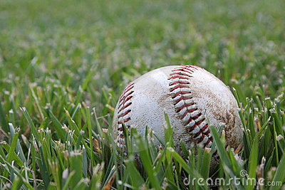 Closeup of used baseball on the grass