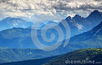 Bluish mist and dark clouds over forested ridges Dolomiti Italy