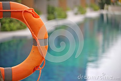 Lifebuoy,Life preserver,Life ring,Life belt hanging at the public swimming pool in the blur background. To show concept of safety