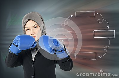 Young woman with boxing glove and aggrasive face expression over abstract background