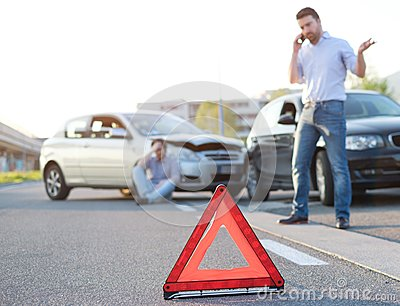 Men calling first aid after a bad car crash on the road