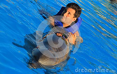 Green eyes man swimming with a gorgeous dolphin flipper smiling face happy kid swim bottle nose dolphins