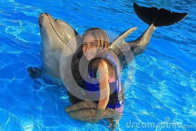 Little girl children hugging a gorgeous dolphin flipper smiling face happy kid swim bottle nose dolphins