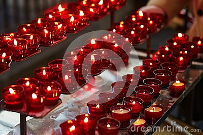 Church candles in red chandeliers