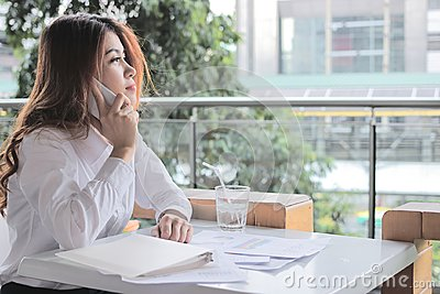 Side view of attractive young Asian business woman talking on mobile smart phone against partnership on the desk in office with co