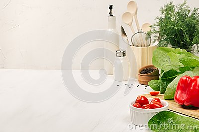 Kitchen white interior with raw fresh green salad, red cherry tomatoes, kitchenware on soft white wood table, copy space.