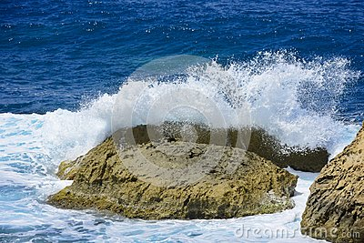 The wave is broken on the stone with a spray