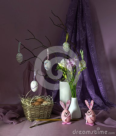 Easter composition with eggs in a wicker basket, church candles, twigs in a vase and flowers freesia