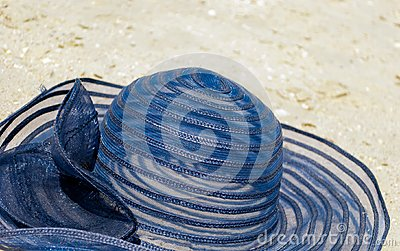 female straw hat blue hat lies on the sand casts a shadow on a bright day beach holidays