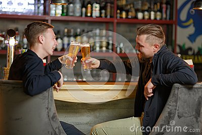 Two cheerful men of friends, sit in a bar, drink a refreshing cold beer and clink glasses.