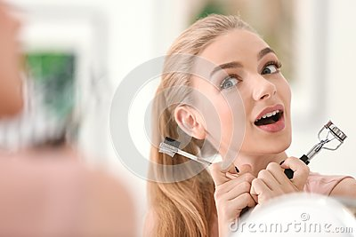 Emotional young woman with eyelash curler and comb