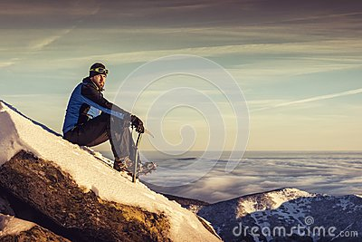 Man seating on top of mountain, male hiker admiring winter scenery on a mountaintop alone with ice ax