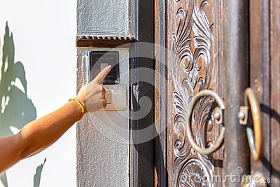 Close up of hand female pushing the button to open the door at the front home