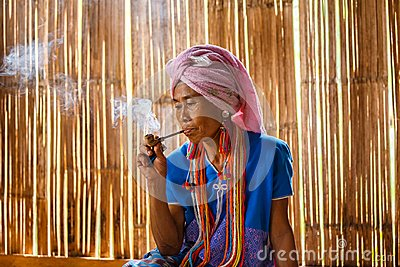 Female karen hill tribe is smoking tobacco pipe traditional in the cottage of northern Thailand at Mae Klang Luang