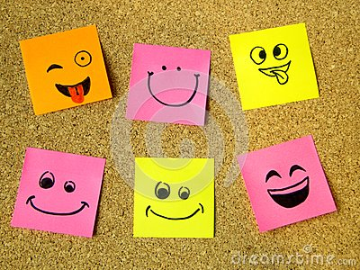 stock image of cork board with colorful post its representing various emoticons with various emotions communication concept