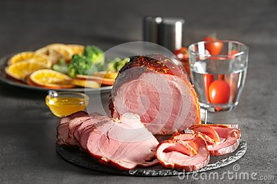 Plate with yummy sliced honey baked ham on table
