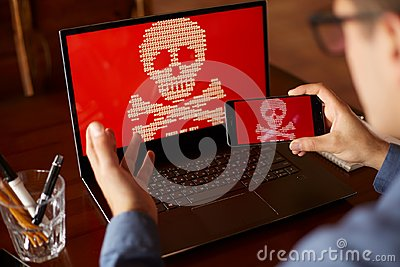 Man sits near laptop with phone blocked and encrypted by ransomware spyware asking for money. Laptop and smartphone