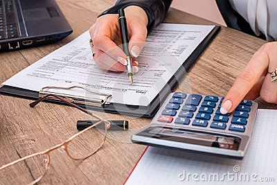 Woman filing individual income tax form 1040, with calculator