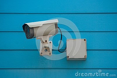 Old Closed Circuit Television Camera or Security CCTV camera setting on  blue wooden background.
