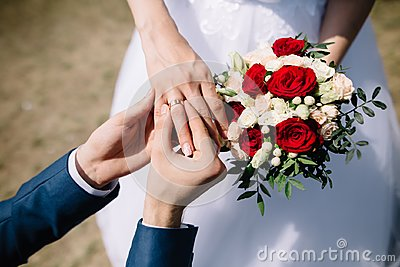 Love and marriage. Fine art rustic wedding ceremony outside. Groom putting golden ring on the bride`s finger. Bouquet of red and