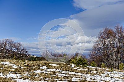 Majestic view of cloudy sky, winter mountain, snowy glade, conifer and deciduous forest from Plana mountain toward Vitosha